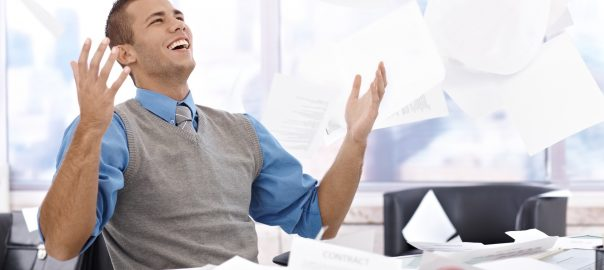 Happy businessman sitting at desk, throwing documents up in air, laughing, celebrating.